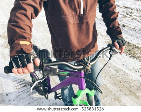 Close up view of incognito man with mountain bike and hare toy tied up on handlebar. Copy space