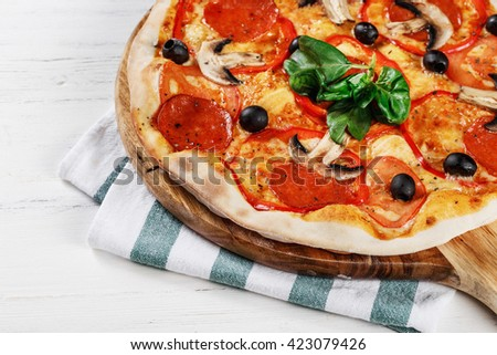 Close-up view of  ITALIAN PIZZA on wooden table. True hot tasty PIZZA with salami, mushrooms, basil, olives, pepper and cheese. Nice for menu Pizzeria. High quality