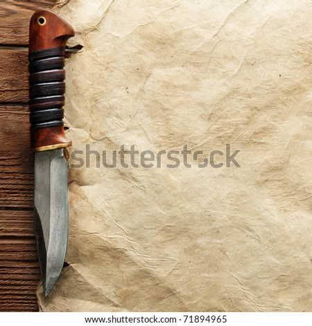Close up view of knife on vintage paper