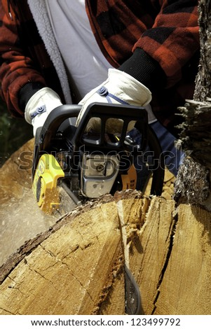 Close-up view of lumberjack with electric saw - stock photo