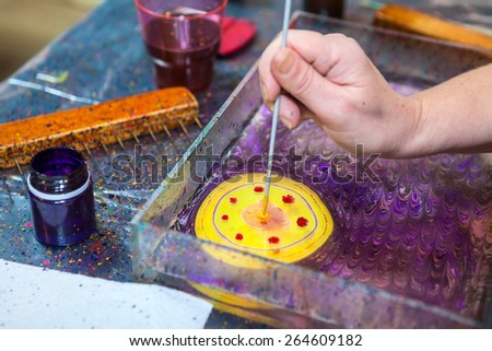 Close-up view of making pattern with inks on water surface - stock photo