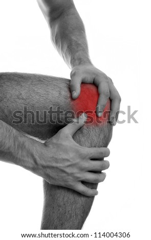 Close up view of male hands holding his sore knee. - stock photo