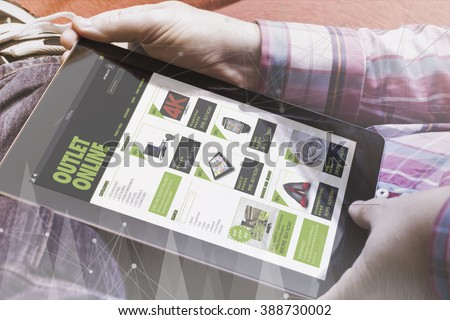 close-up view of man holding a tablet showing outlet online site. Digital commerce concept. All screen graphics are made up.