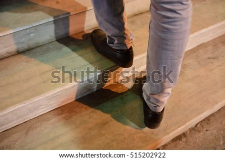 Close-up view of man's walking upstairs