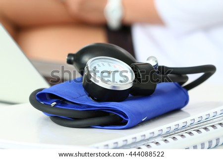 Close up view of manometer laying on working table. Hospital workspace. Healthcare, medical service, treatment, hypotonia or hypertension concept. Female doctor operating on background. Copyspace - stock photo
