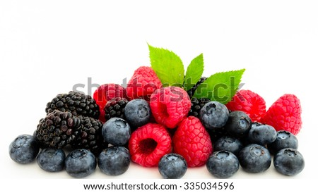Close-up view of mixed, assorted berries blackberry, strawberry, blueberry, raspberry with green leave isolated on white background. Colorful and healthy concept. Black, blue, red, green color