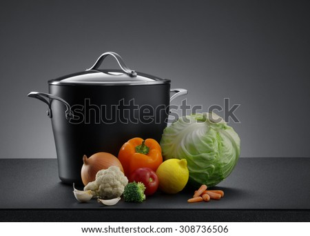 close up view of nice cookware with some vegetables on grey color back - stock photo