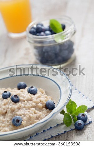close up view of oatmeal porridge with strawberry on color back - stock photo