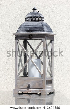 Close up view of old fashioned wooden Lantern with a burning candle. - stock photo