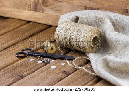 Close-up view of old sewing kit: scissors, twine, thread, buttons, sackcloth on wooden background - stock photo