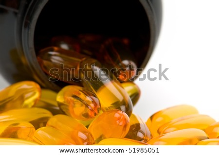Close up view of Omega 3 pills, spilling from bottle. Use of selective focus. - stock photo