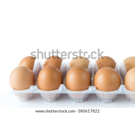 Close-up view of organic Brown Eggs on Plastic Egg Carton isolated on white background. Selective focus and shallow DOF. Copyspae. - stock photo