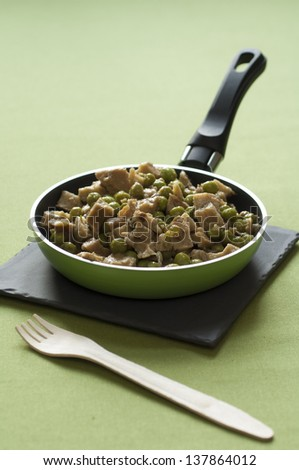Close-up view of organic Seitan chops with green peas in a hot pan placed on a stone dish with a wooden fork - stock photo