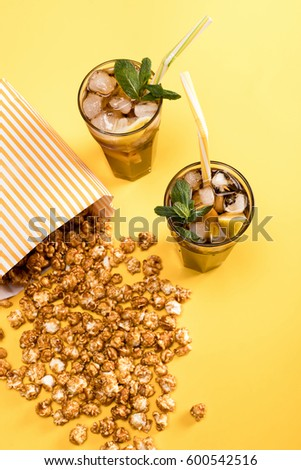close up view of popcorn and iced tea in glasses isolated on yellow, Movie time concept