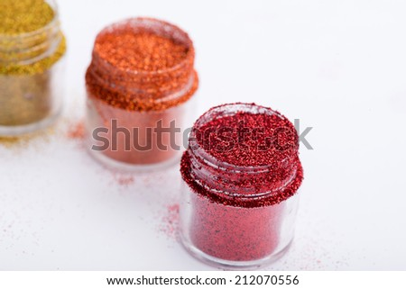 Close-up view of  powder eye shadows  in red, orange and yellow colours isolated on white background with selective focus on red powder eyeshadow  with copy place - stock photo