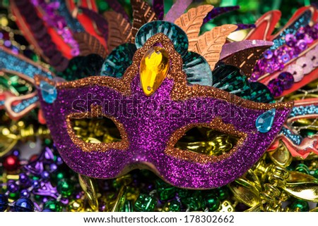 Close up view of purple sequined Mardi Gras mask with colorful beads out of focus in the background - stock photo