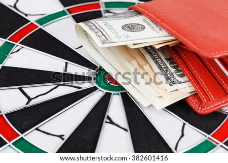 Close up view of red arrow and one hundred dollar bill on dart board. - stock photo