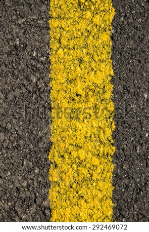 Close up view of road texture with yellow stripe.