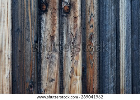 Close-up view of rough textured wood plank fence. Wood panels show various colors and stages of weathering, from darker, medium browns to light colored sections. Horizontal background image. - stock photo