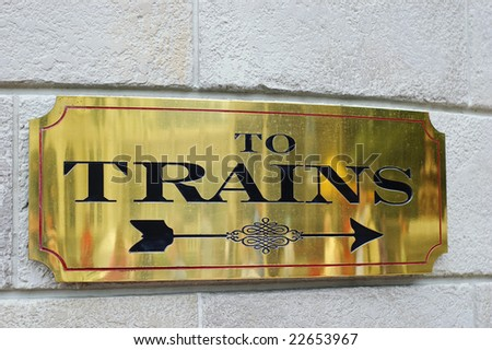 Close-up view of sign indicating direction to board trains