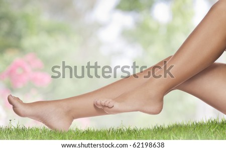 close up view of smooth womanâ??s legs on color background