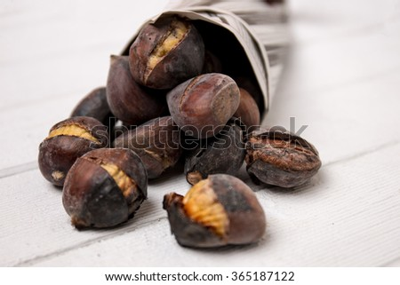 Close up view of some delicious hot toasted chestnuts wrapped on newspaper. - stock photo