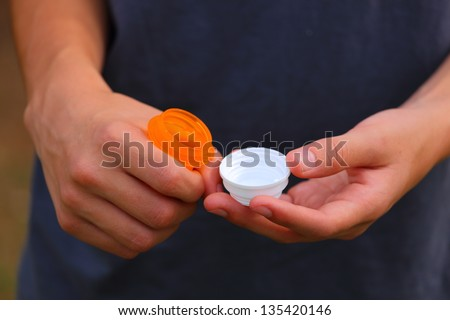 Close up view of someone opening up an orange prescription bottle with a white top - stock photo