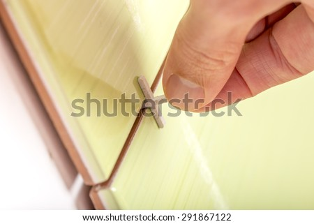 Close up view of  spacers being used by a tiler while tiling a wall to ensure an even gap for the grout between the tiles. Suitable for  DIY and home renovation concept.  - stock photo