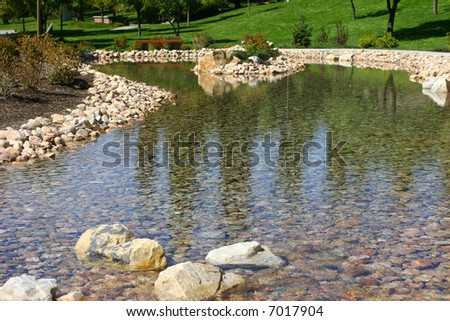 close-up view of stream of water in rock bed with green grass - stock photo