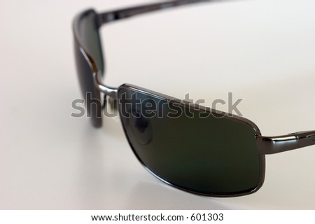 Close-up view of sunglasses sitting on a white surface, viewed from above. - stock photo
