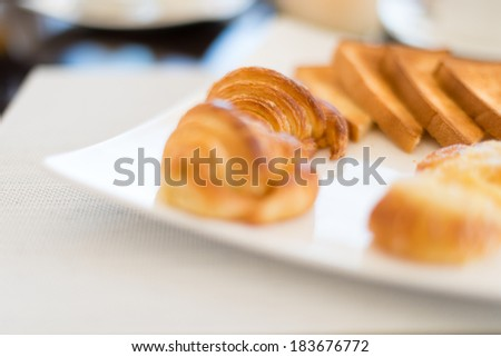 Close-up view of tasty croissants and toasts on square plate served on table with white mat. Fresh appetizing pastry with crisp for breakfast in cafe or restaurant. Delicious food and French cuisine. - stock photo
