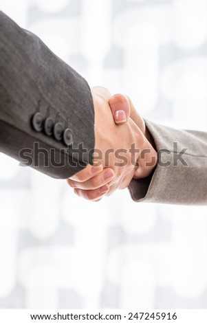 Close up view of the arms of two businesspeople in suits shaking hands over a blurred abstract background conceptual of a deal, agreement, partners or greeting, vertical format with copyspace. - stock photo