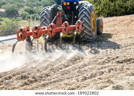 Close up view of the blades of a plow on a tractor plowing an agricultural field tilling the land in preparation for planting the spring crop - stock photo