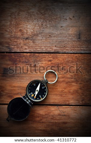 Close up view of the Compass on the old wooden background - stock photo