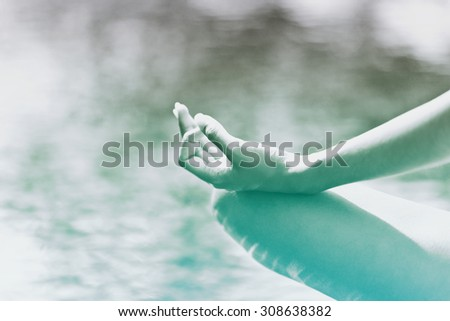 Close up view of the graceful hand gesture of a woman meditating overlooking a pool with tranquil blue sunlit water - stock photo