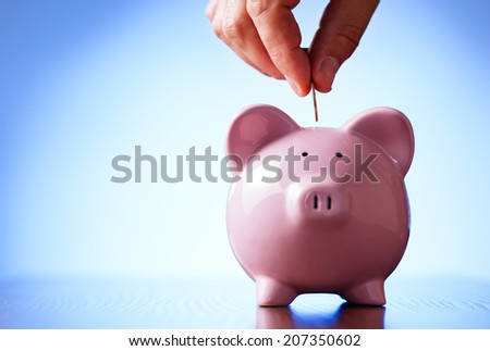 Close up view of the hand of a man placing a coin into the slot of a piggy bank in a savings and investment concept - stock photo