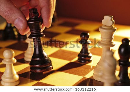 Close up view of the hand of a man playing chess making a move holding the black king in his hand - stock photo