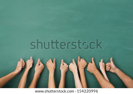 Close up view of the hands of a group of people giving a thumbs up gesture of approval an success with their hands raised against a blank green chalkboard with copyspace - stock photo