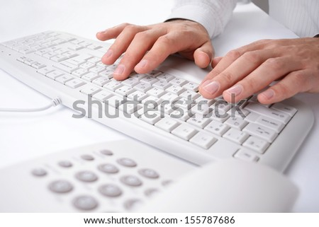 Close up view of the hands of a man entering data on a computer keyboard as he works at his desk with a telephone in the foreground
