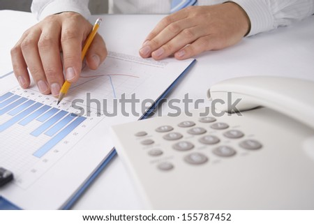 Close up view of the hands of a young businessman sitting at his desk analysing a bar graph