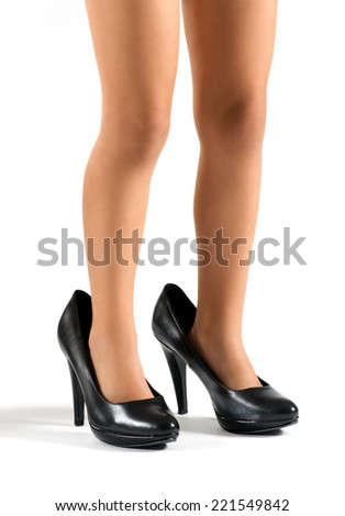 Close up view of the legs of a little girl wearing her mothers classic black high heeled shoes several sizes too big for her, over white