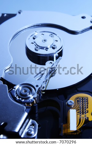 Close-up view of the opened hard disk drive(toned in blue mode shallow dof) - stock photo