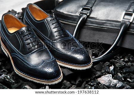 Close-up view of the pair stylish and elegant men's shoes and  bag for business meetings and business lifestyle - stock photo