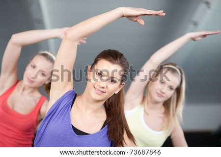 Close up view of three beautiful young woman doing aerobics exercises - stock photo