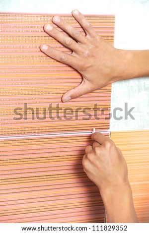 Close-up view of tiler hands fixing wall tile with spacers at home repair renovation work - stock photo