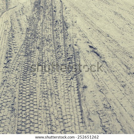 Close up View of Tire Tracks Prints in Sand, Vintage toning - stock photo