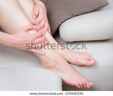 Close up view of tired woman legs on the sofa - stock photo