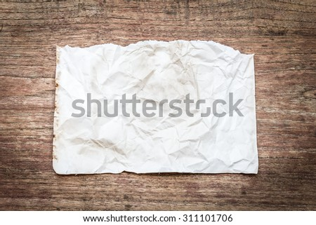 Close up view of torn piece of old paper for massage on wood background