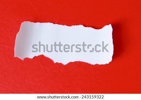 Close-up view of torn piece of paper for ??message on red - stock photo
