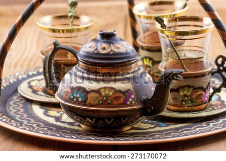 Close-up view of traditional Turkish tea set: vintage glass cups with teapot on the plate - stock photo
